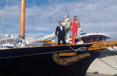 Models having a photoshoot on the bow of Schooner America 2.0